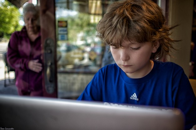 Boy on laptop in coffeeshop